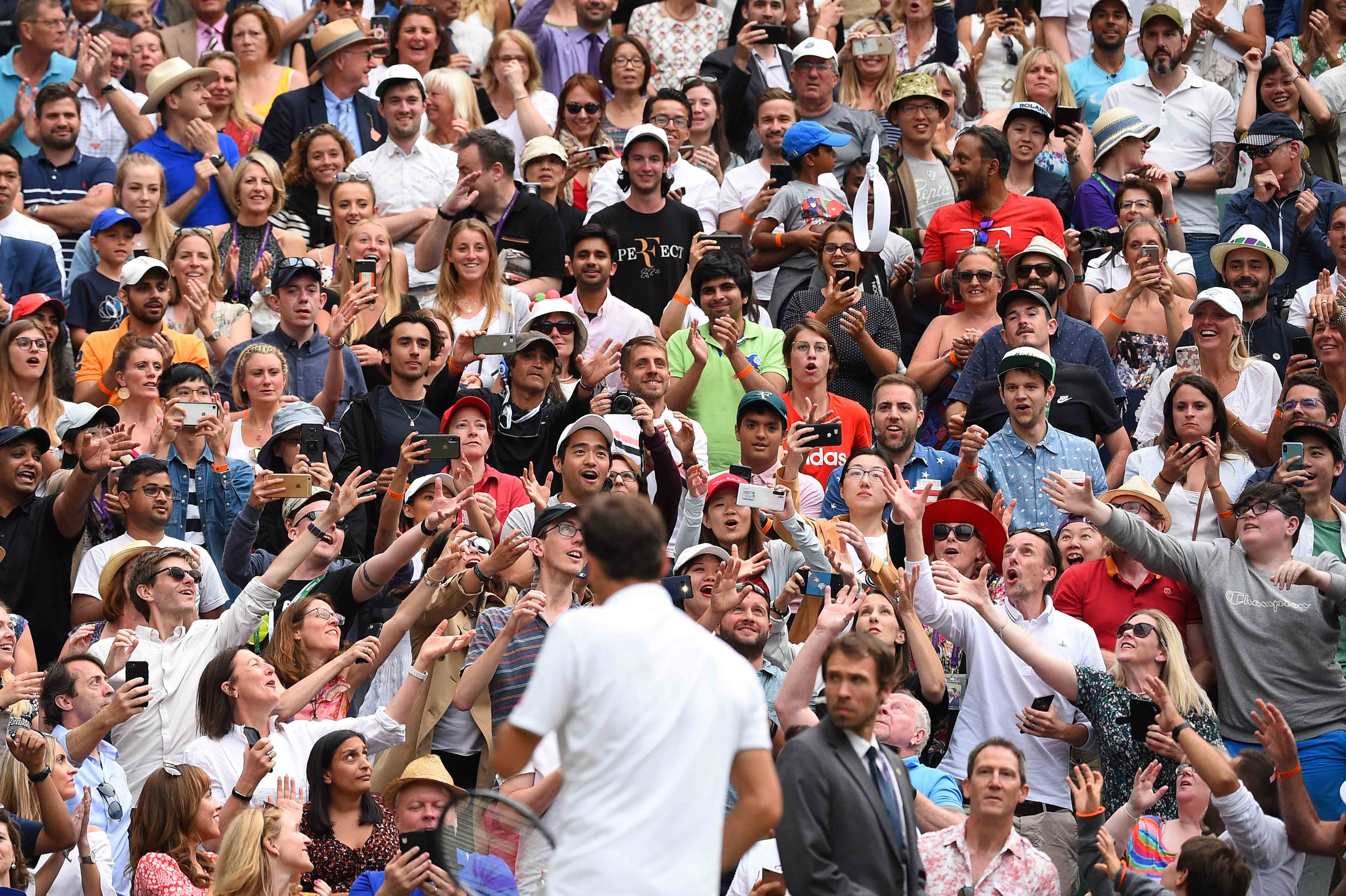 Astonished crowd as Roger Federer throws his headband to them at Wimbledon 2019.
