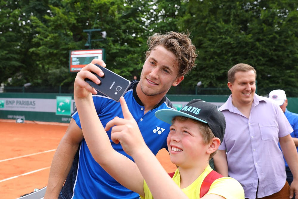 Casper Ruud poses with a fan after winning his second-round qualifying match at Roland-Garros 2018.