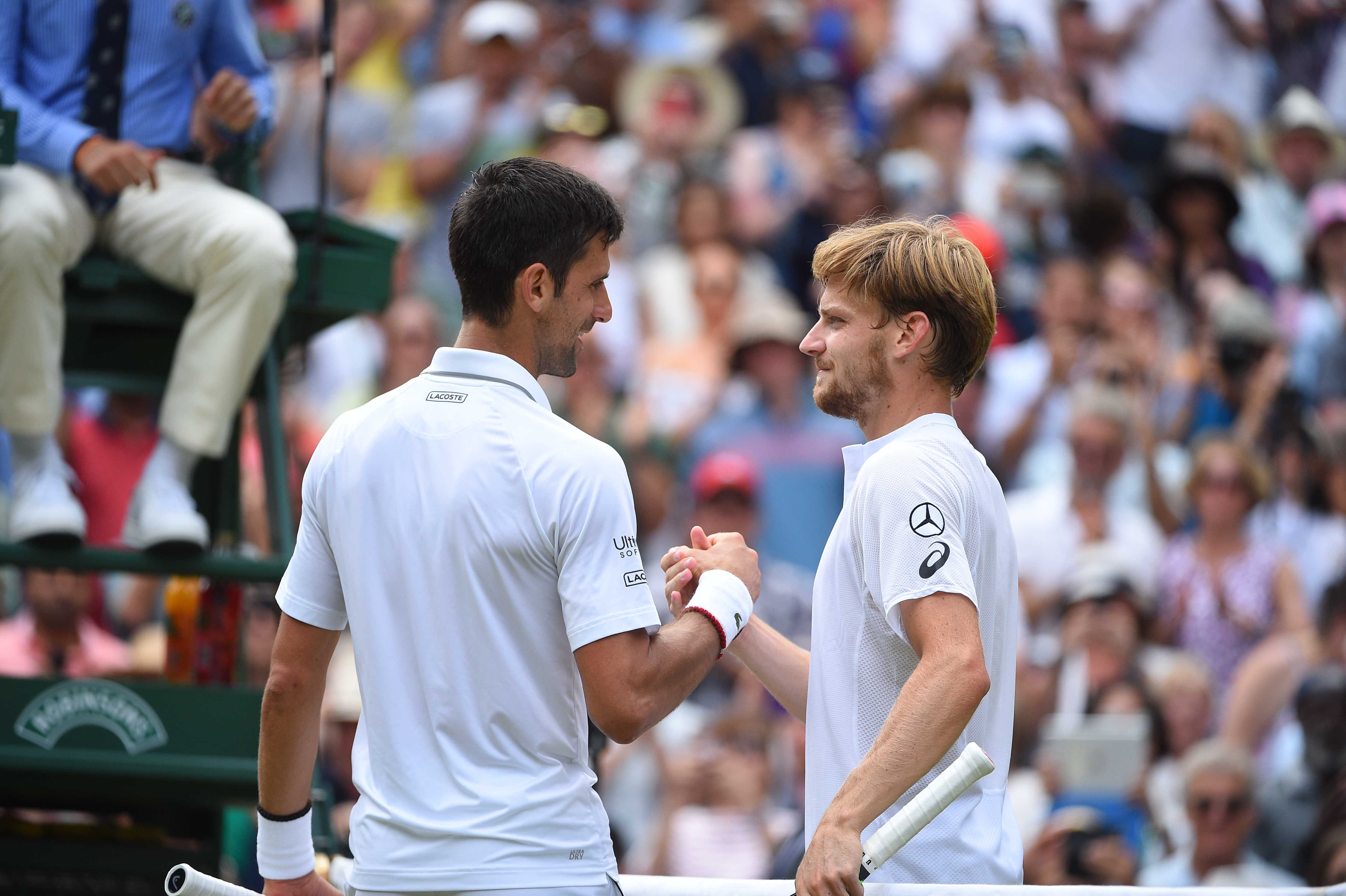 Novak Djokovic and David Goffin at the net at Wimbledon 2019.