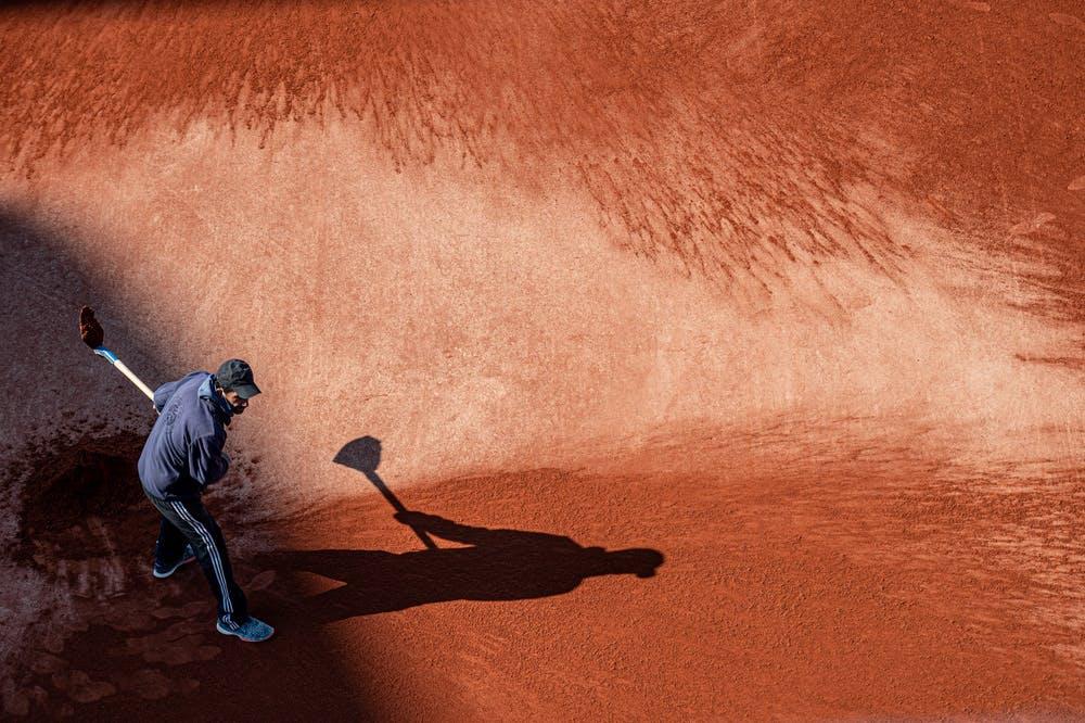 Un homme d'entretien prépare la terre battue avant Roland-Garros 2021