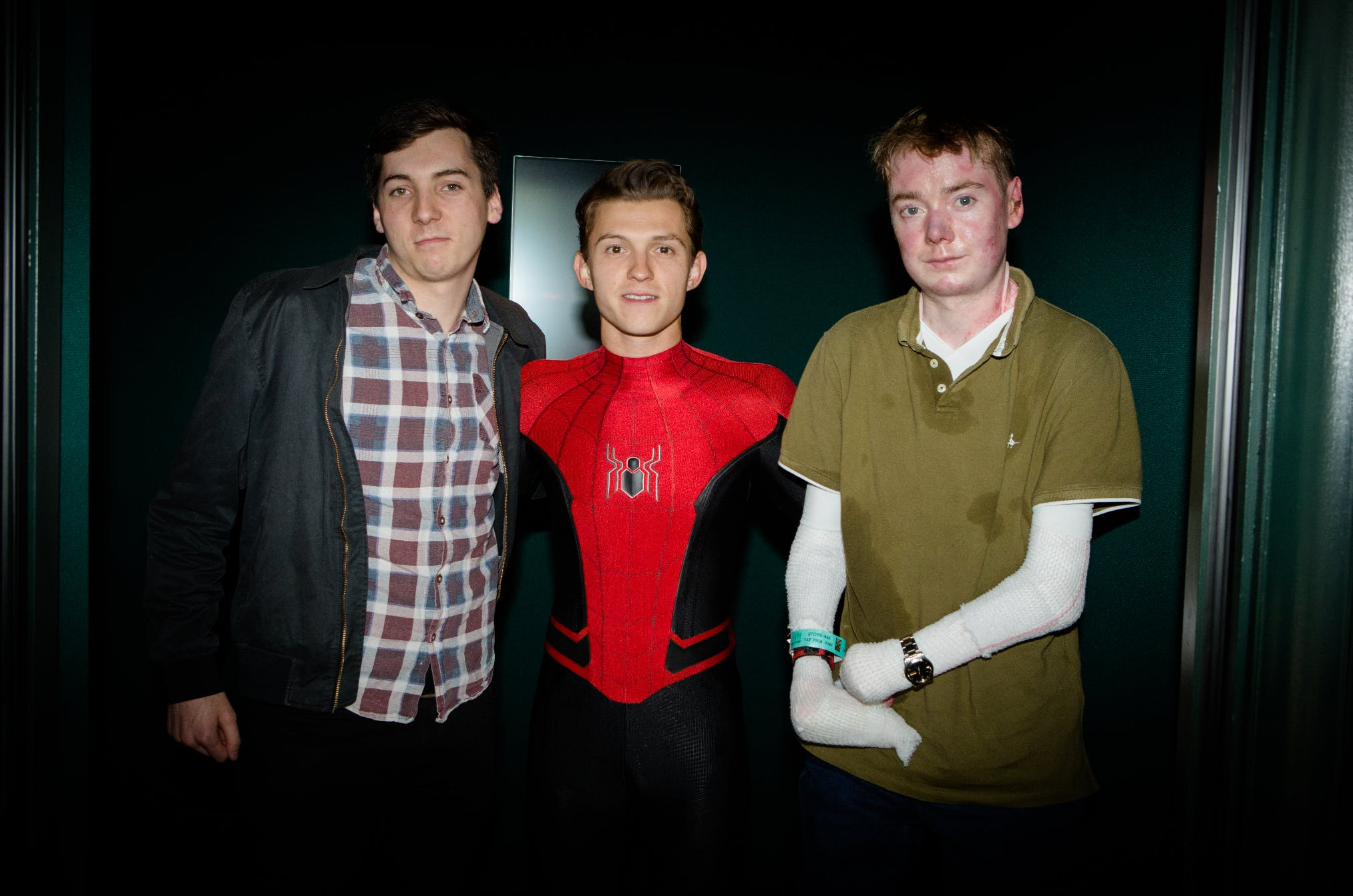 Actor Tom Holland dressed as Spiderman standing between two men - one in a check shirt and one in an olive shirt.