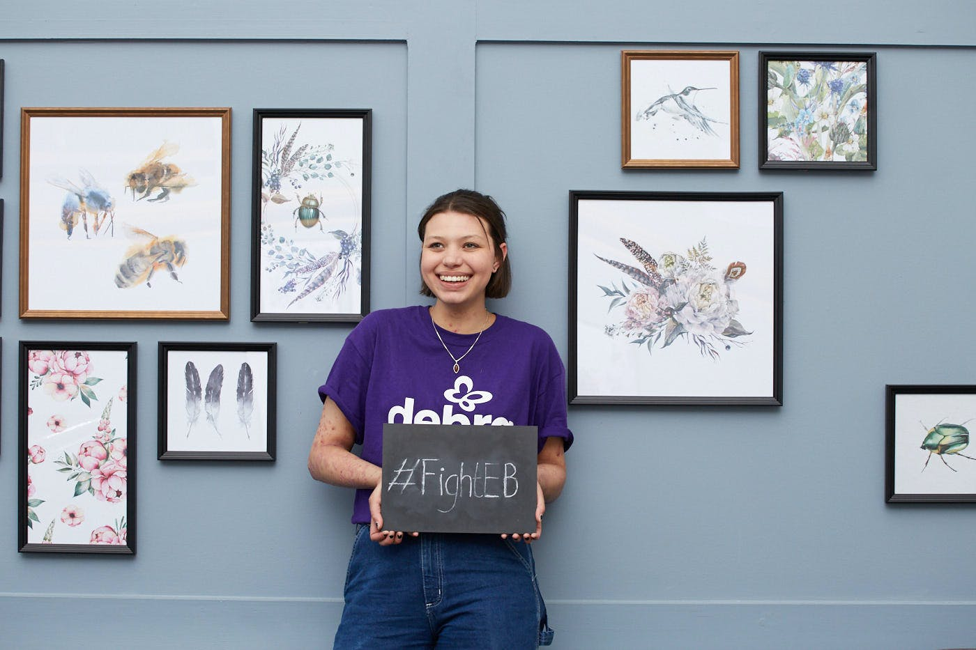A girl leaning against a lavender coloured wall holding a chalk board that says '#FightEB'. The wall has paintings hanging on it.