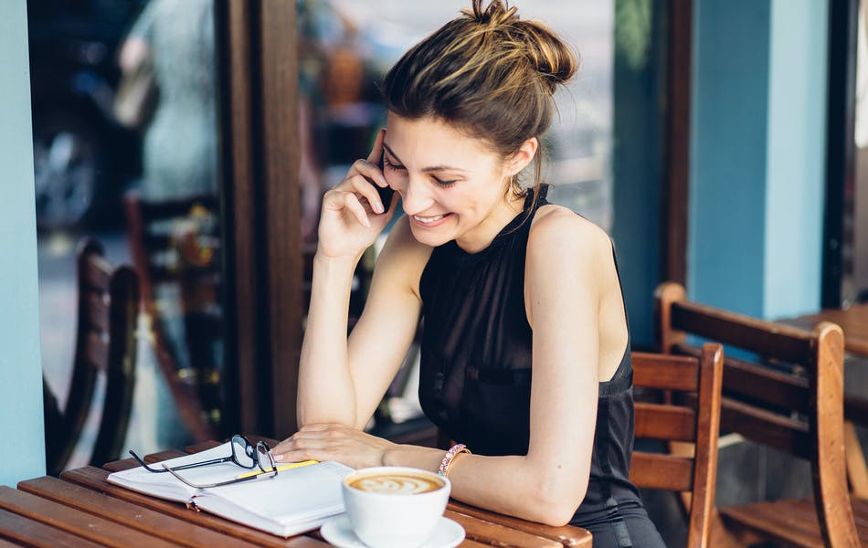 woman at a cafe talking on the phone
