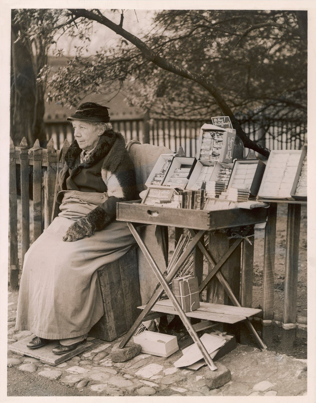 A sepia-toned photograph of an older woman sitting on a wooden crate by the side of the street. She is wrapped up warmly in a hat, jacket, and gloves, with a blanket over her lap. Next to her is a small folding table with boxes of chocolate for sale.