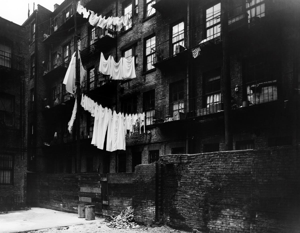 Black and white photograph of tenement housing, with laundry lines strung between balconies.