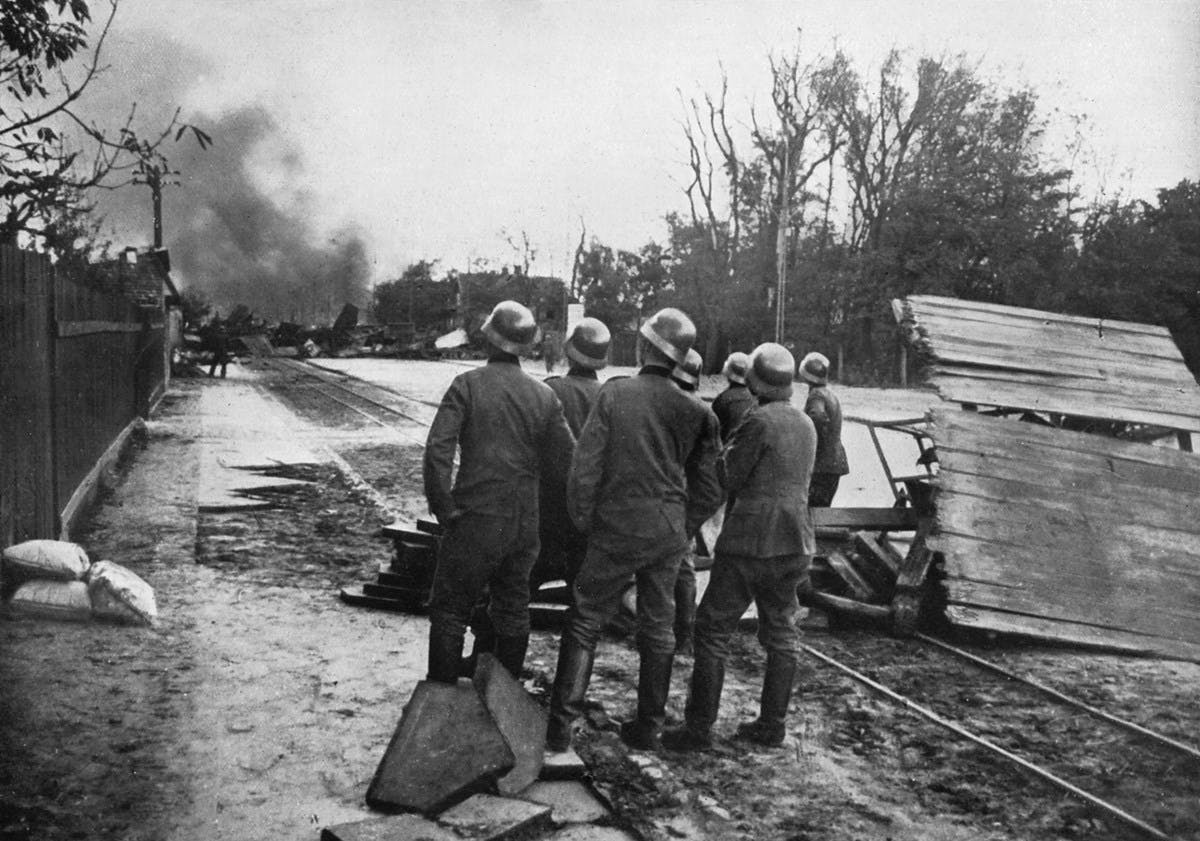 A black-and-white photograph showing a small group of German soldiers looking at smoke in the distance.