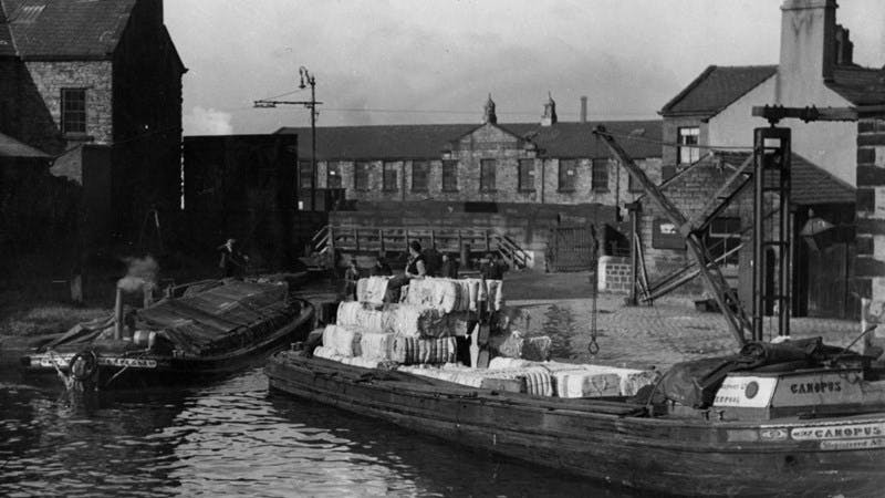A black-and-white photograph showing a barge being loaded with bales of cotton.