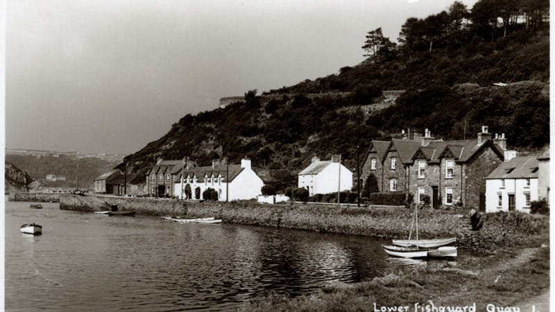 A black-and-white photograph of a small group of houses running along the water.