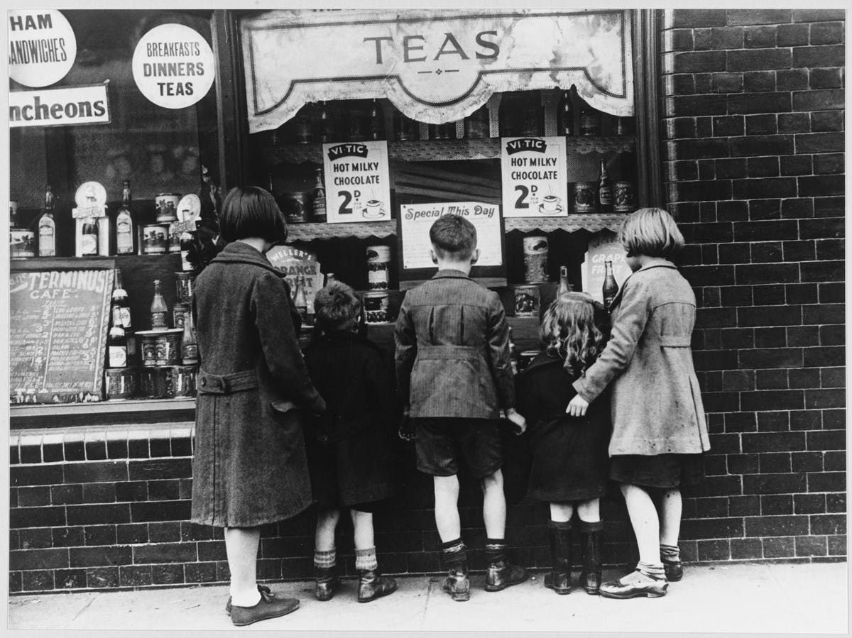 A black-and-white photograph of children looking in the window of a cafe. The cafe has an awning advertising 'Teas' and there are signs in the window advertising 'Hot Milky Chocolate'.