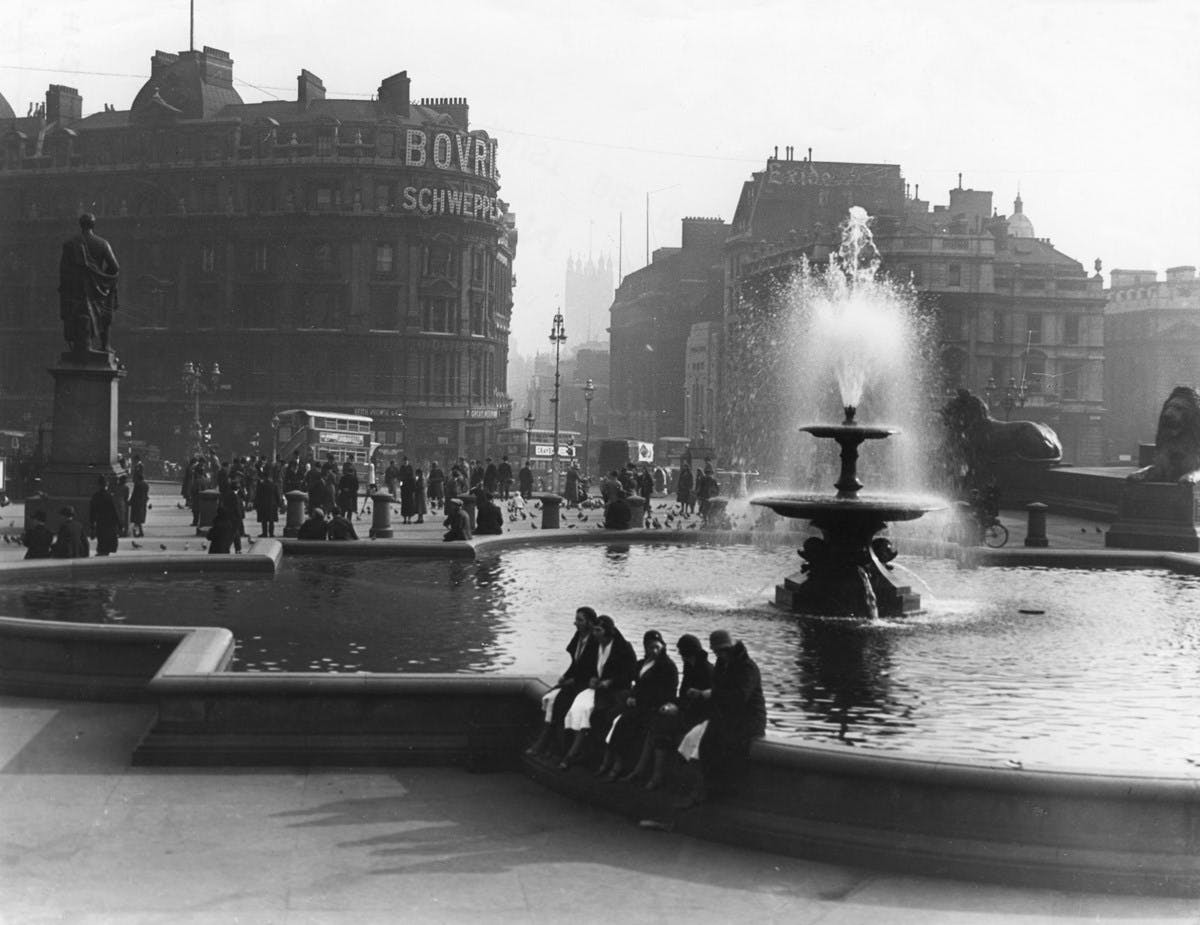 A black-and-white photograph of Trafalgar Square. The fountain is in the foreground, with a few people sitting on the edge and talking. In the background there are many more people milling around. On the side of a building there are large, lit adverts for 'BOVRIL', and 'SCHWEPPES'.