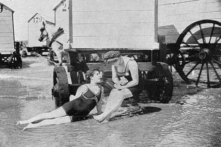 Vintage photo of women and bathing machines at the beach.