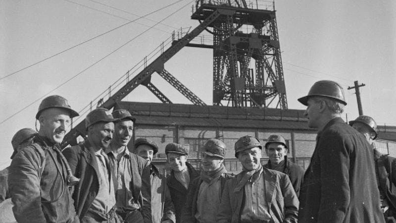 A black-and-white photograph of coal miners smiling outside a colliery.