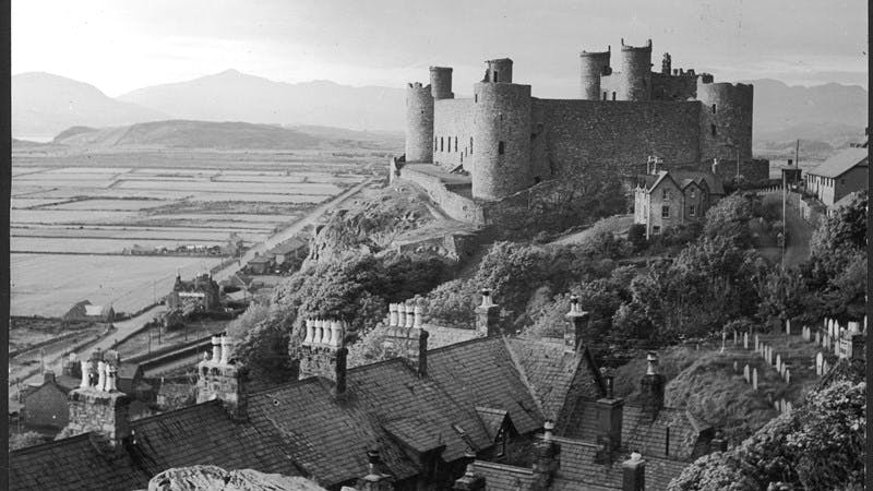 A black-and-white photograph showing Harlech Castle atop a hill in the foreground, with fields and hills stretching off to the horizon.