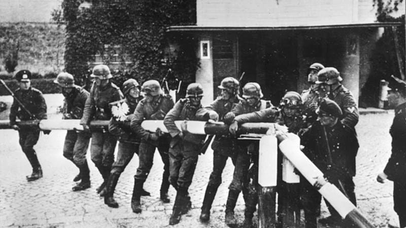 A black-and-white photograph showing a dozen German troops pulling down a turnpike at the German-Polish border.