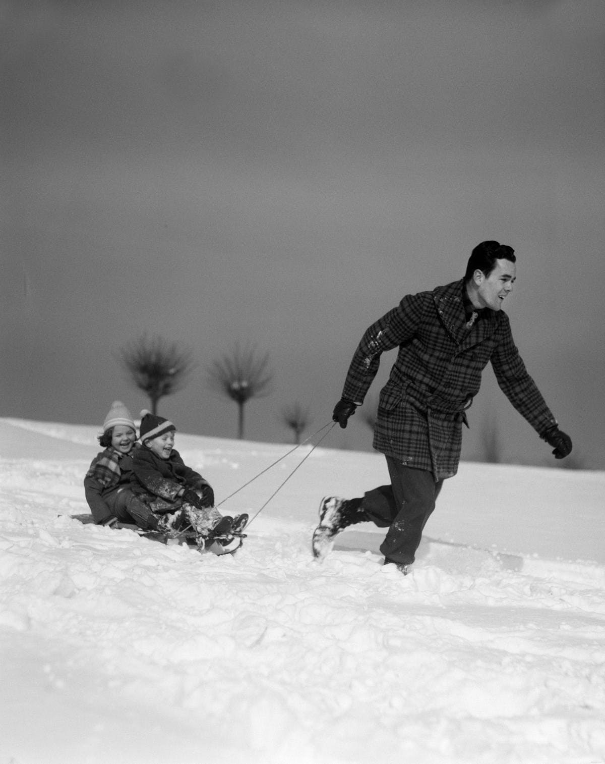 A black-and-white photograph of a young father pulling his two children on a sledge through a snowy landscape.