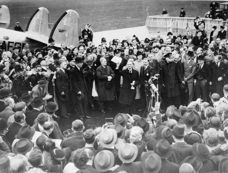 Black and white photograph of Neville Chamberlain talking to a crowd.