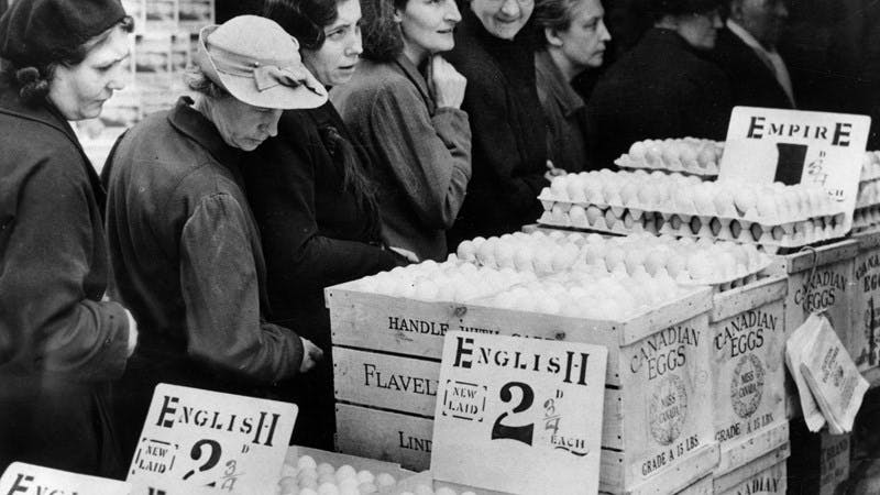 Black and white photograph of women looking at crates marked 'Canadian Eggs'