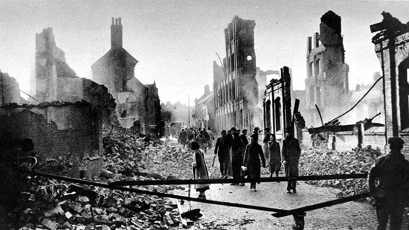 A black and white photo of a road in the centre of Coventry after the German air-raid of 14th November 1940. This is a scene of destruction. Only the facade of a few buildings remain standing. There is rubble everywhere. A large amount of people are walking through the space in the middle of the street.