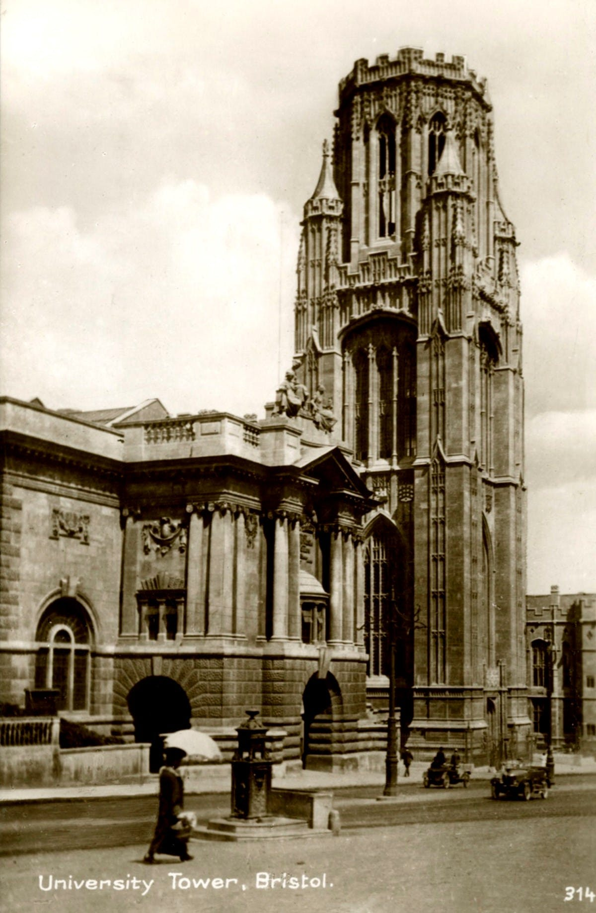 A sepia-toned photograph showing the University Tower in Bristol. A road in front of it has two cars upon it, and a woman strolls with an umbrella.