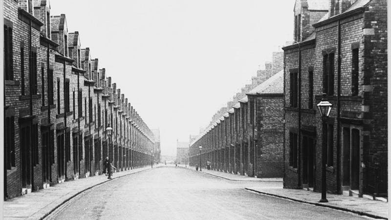 Black and white photograph looking down a street of terraced houses in the 1930s.