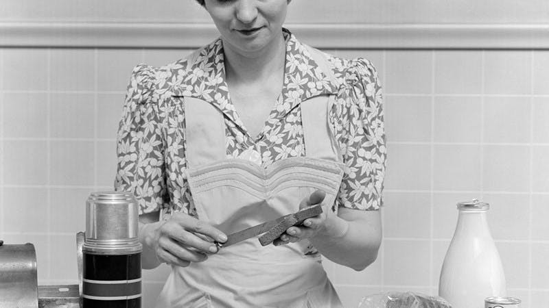 Black and white photo of a 1930s housewife in a kitchen preparing a sandwich and packing lunch. On the counter are a metal lunchbox and thermos bottle, apples, bread and a glass bottle of milk.