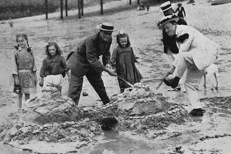 Vintage photo of people building sandcastles