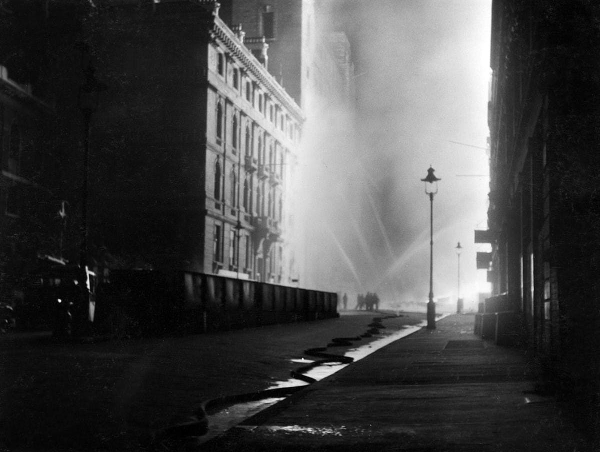 Black and white photo of a group of firemen at Queen Victoria Street, in London, during the night between the 10th and 11th May 1941. The firemen are in the back, spraying water with hoses to stop fires at the third-floor level on both sides of the street.