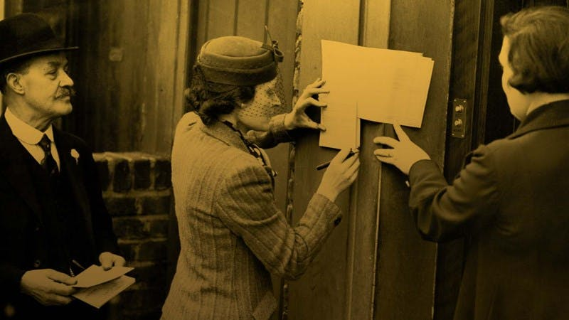 Photo with a yellow tint of three people filling in their 1939 registration papers on a door