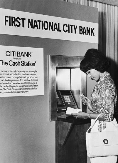 A girl uses an early ATM in the 1960s