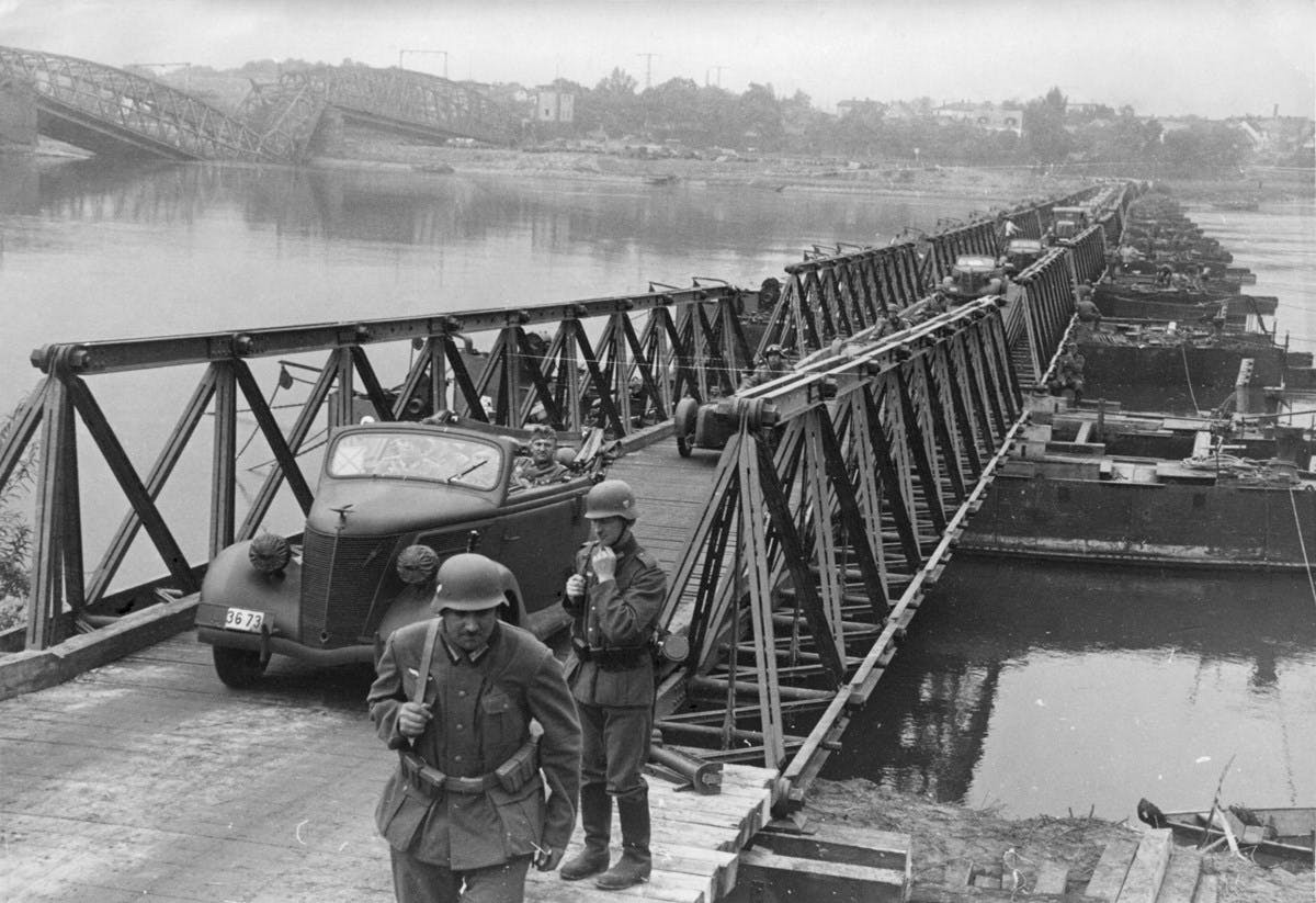 A black-and-white photograph of vehicles crossing over a river.