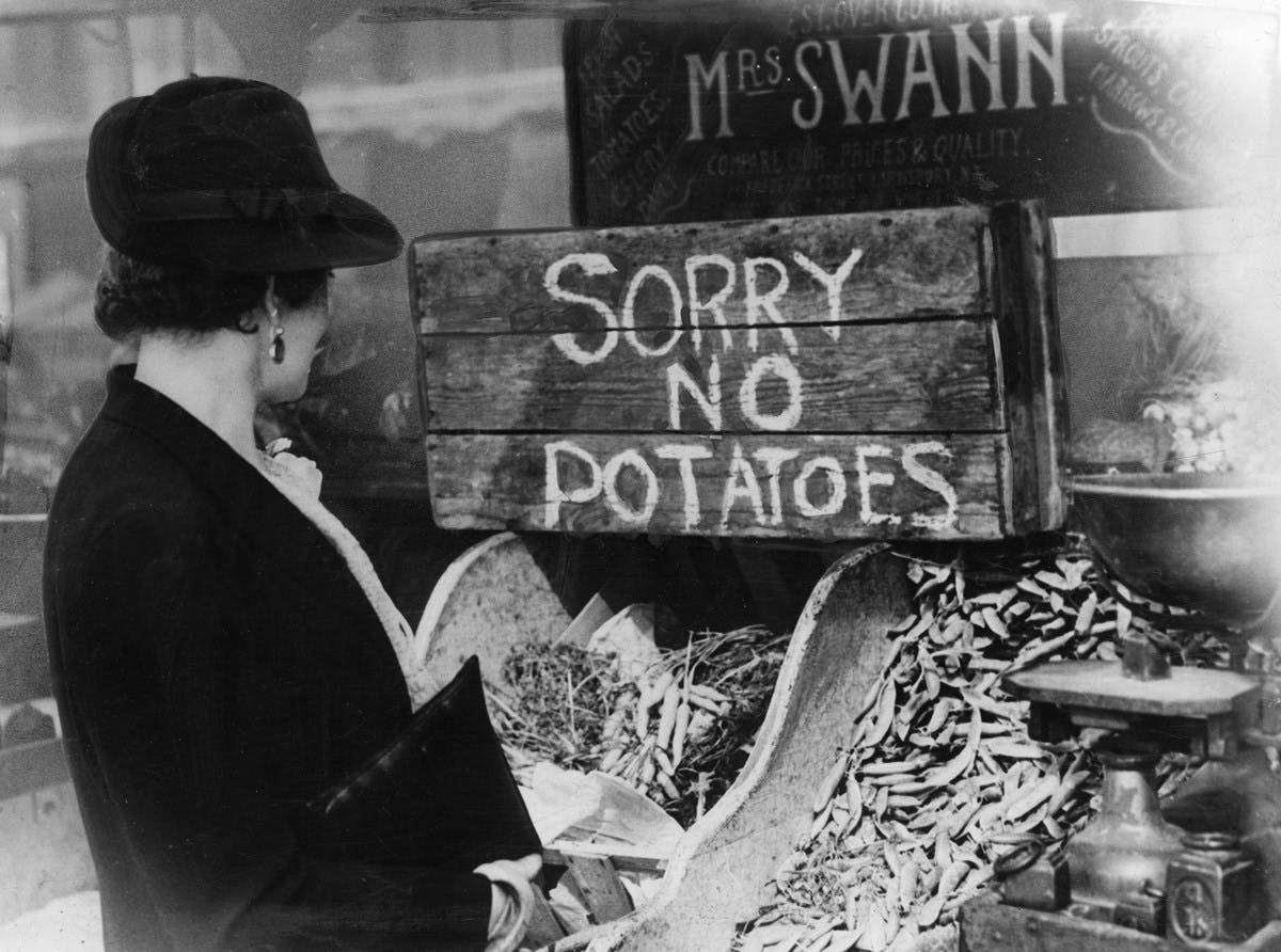 A black and white photograph of a grocery store, where a well-dressed woman looks at empty shelves, with a make-shift sign saying Sorry No Potatoes