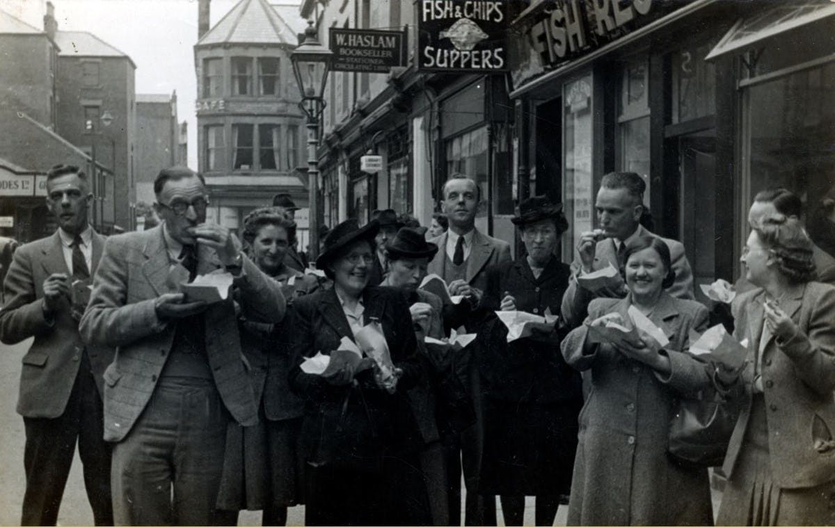 A black-and-white photograph showing a large group of people happily eating fish-and-chips on the street.