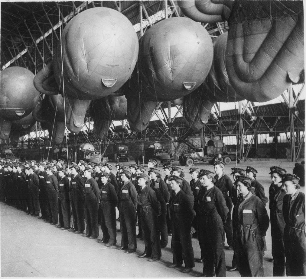 Black and white photo of a W.A.A.F. operators in a hangar. They are all standing still in uniform, with their hands behind their back and in a row as they are reporting for inspection at the end of a day of training. Behind them, the ballons have been tucked away and can be seen floating in the hangar.