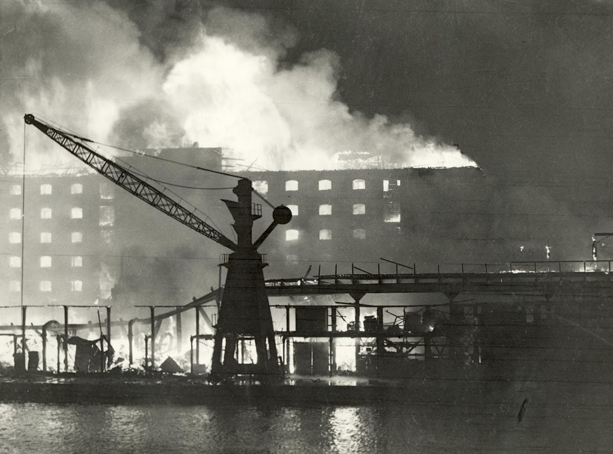 A black and white photo of the Surrey Docks in London at the height of the Blitz. The photo was taken at night, while the buildings were on fire. In the foreground, a crane is visible, with the flames right behind it.