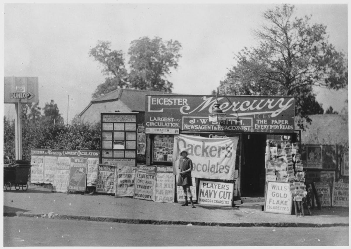 A black-and-white photograph showing a small shop by the side of a road. The shop is covered in adverts like 'Leicester Mercury' and 'Packer's Chocolates', and newspaper headlines. A small stand of postcards is out in front.