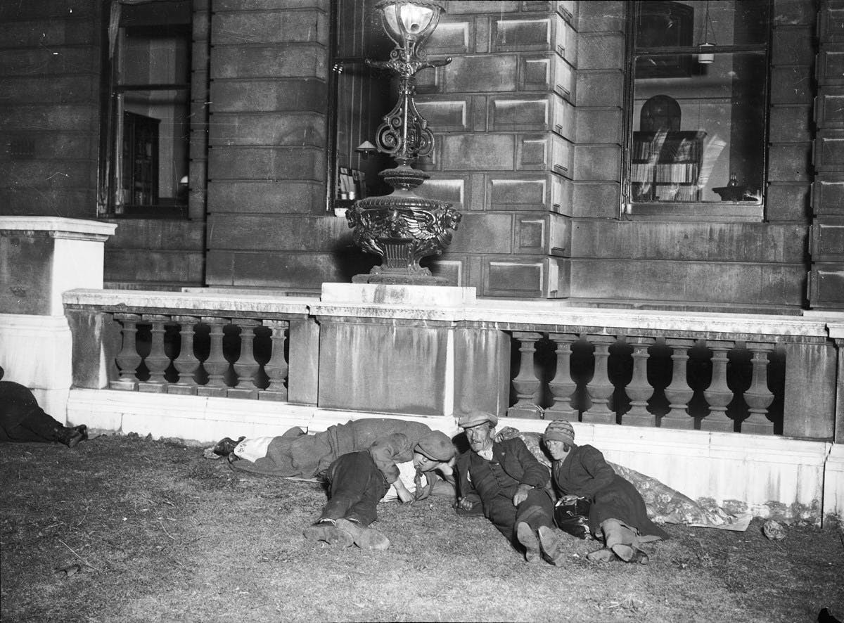 A black and white photo of a group of homeles people sleeping on London's embankment. There are two men and one woman recognisable, but there may be two other persons sleeping under blankets behind them. On the left, the feet of another sleeper are visible.