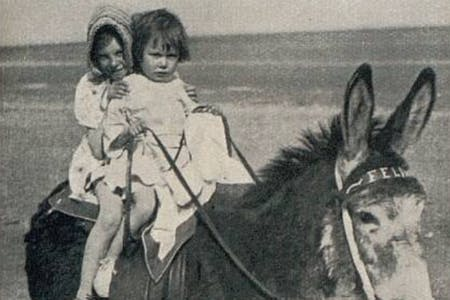 Vintage photo of children riding a donkey at the beach