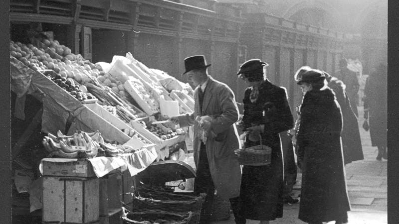 A black-and-white photograph of people in coats and hats looking at fruit and vegetables in a marketplace.