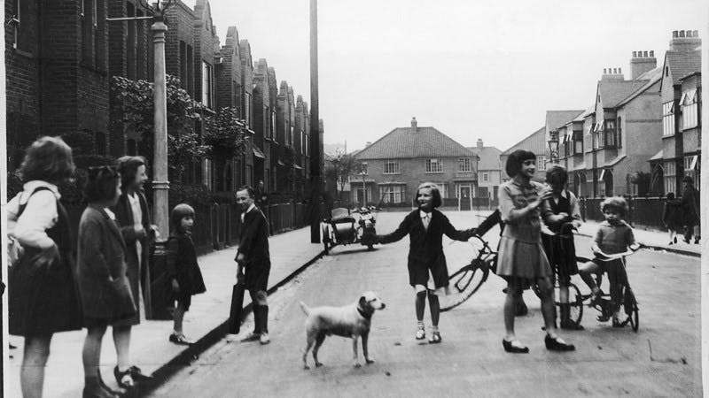 A black-and-white photograph of a group of children playing in a quiet street. There are several bikes, one of them is skipping with a rope, and there is a small dog looking on.