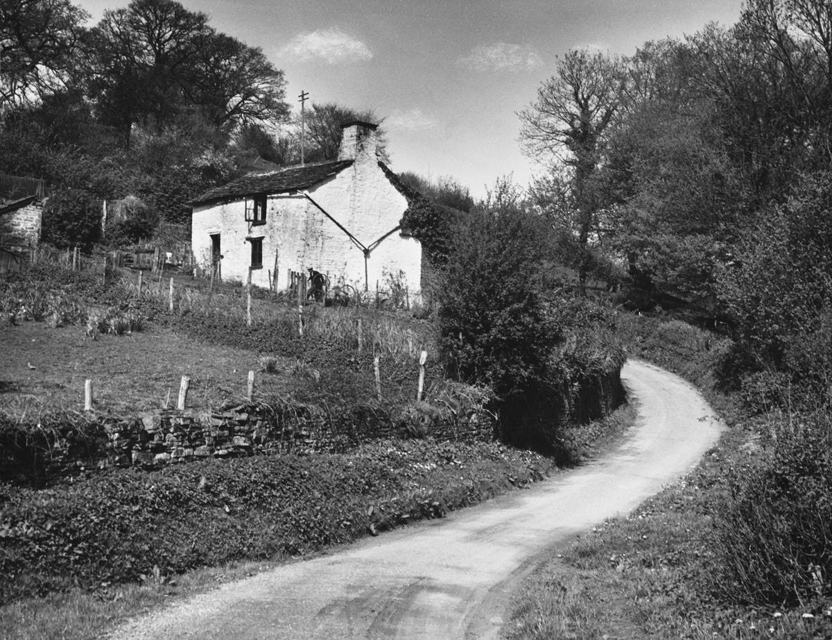 A black-and-white photograph showing a small lane leading up to a small cottage.