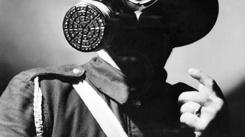 Black and white photo of an Air Raid Warden in uniform, wearing his steel helmet and duty gas mask.