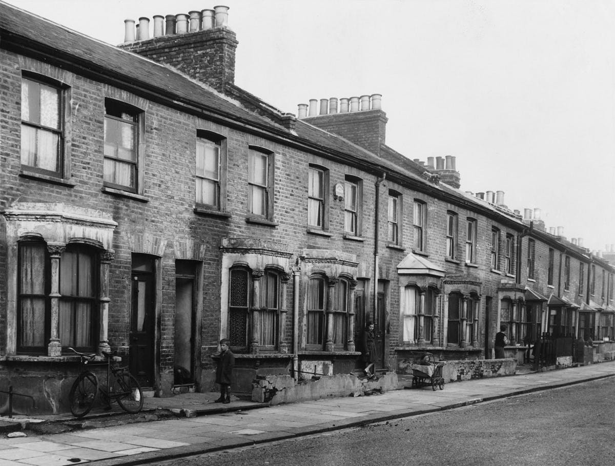 Black and white photograph of a row of run-down terraced houses. A bike rests against a window, and a small boy looks on.