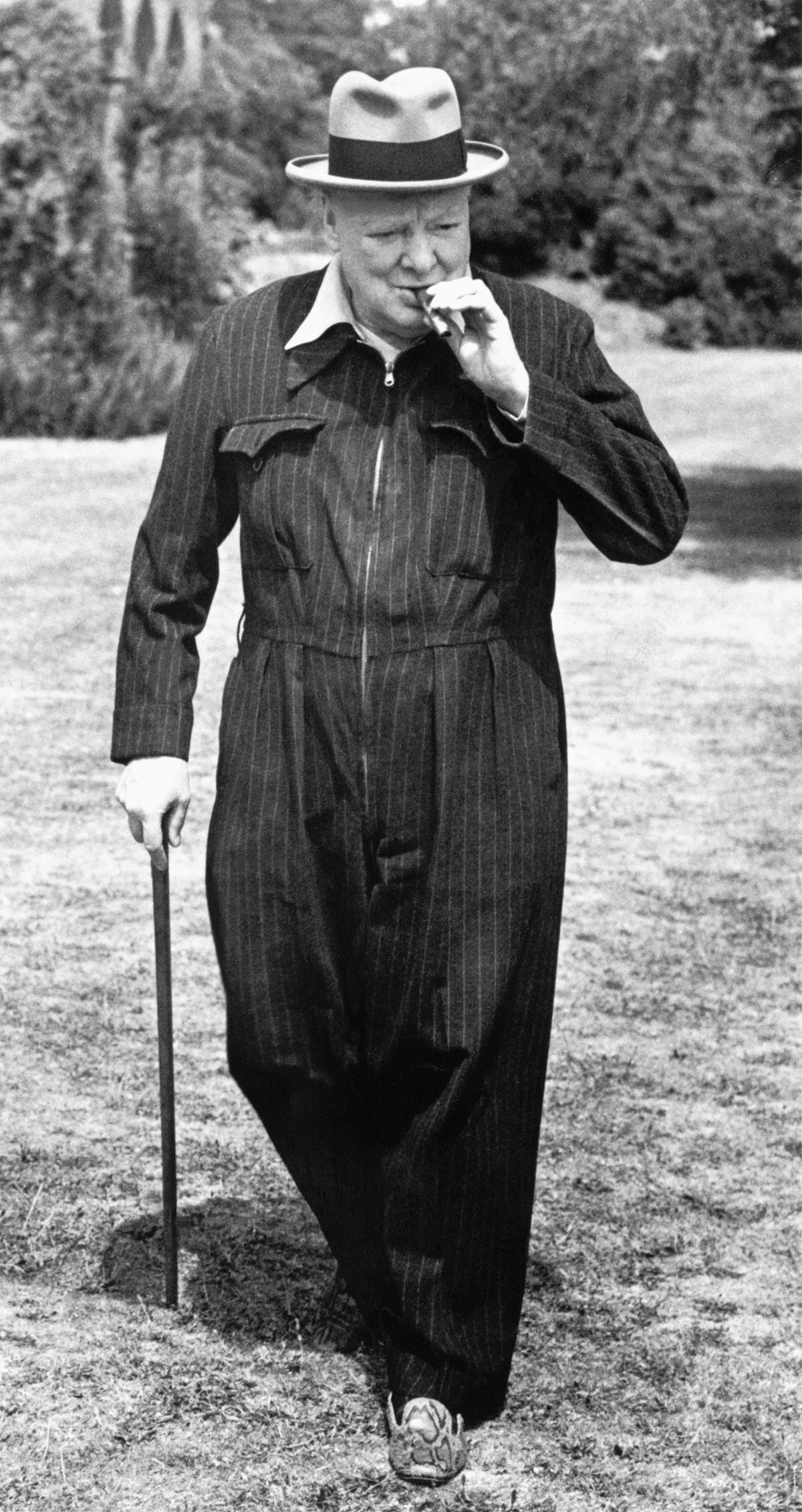 A black and white photograph of Winston Churchill. He is wearing a siren suit, and hat, and is leaning on a cane in his right hand, and is smoking a cigar held in his left.