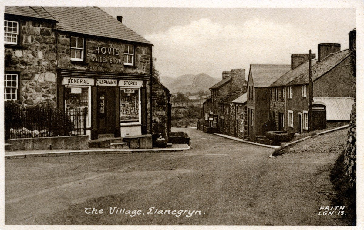 A sepia-toned postcard showing a small village street with some hills visible in the distance.