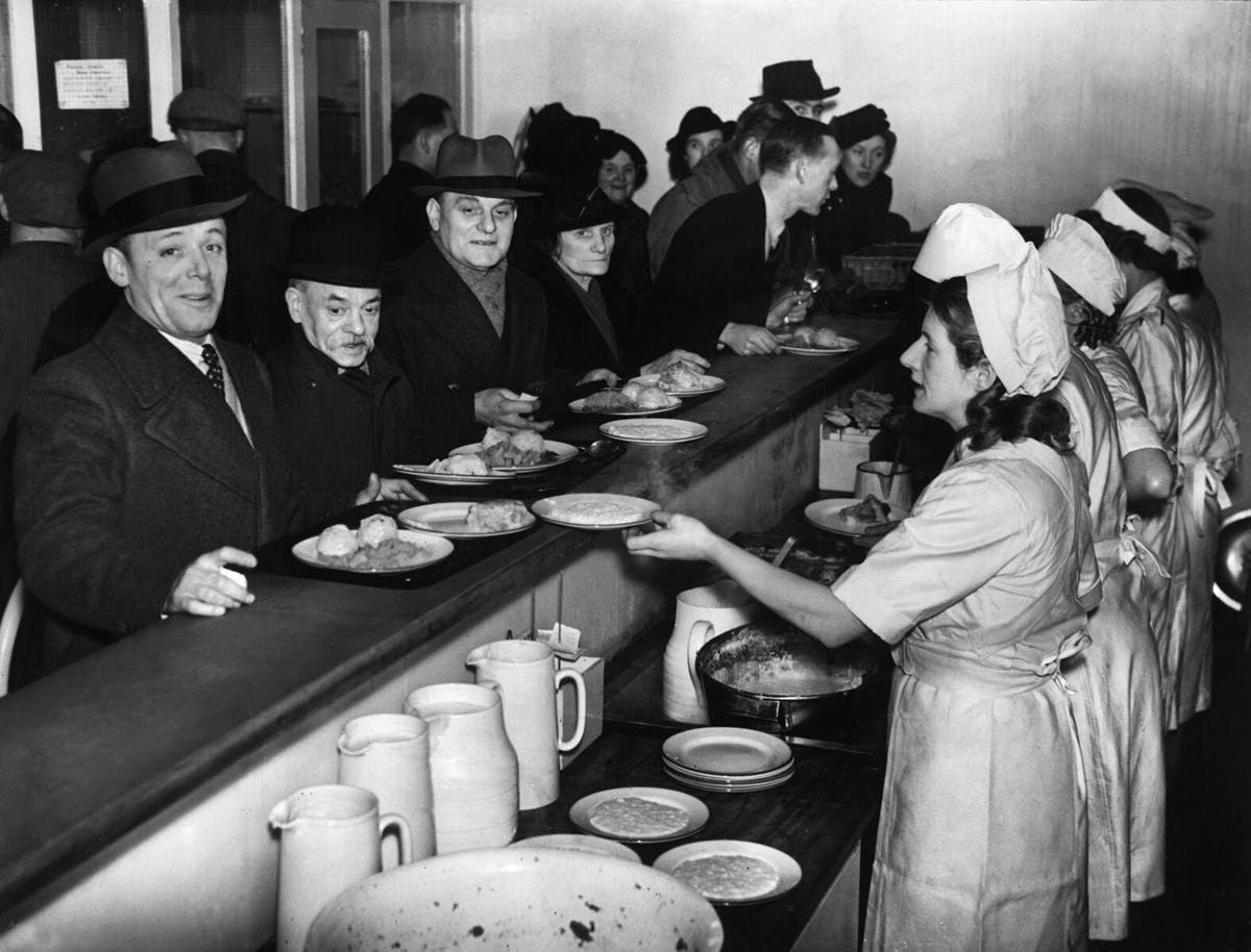 Black and white photo of a group of customers queuing at the service counter at the communal feeding center in Scotland Road, Manchester, on the 5th February 1941.