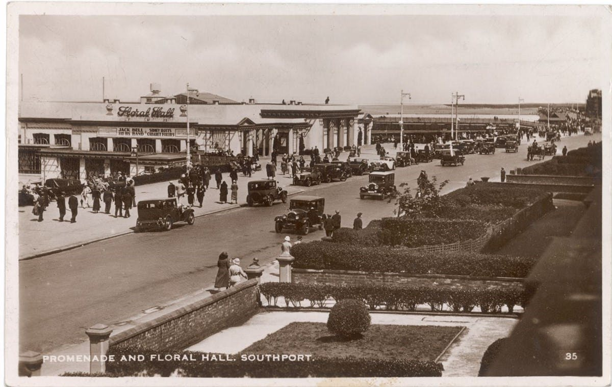 A sepia-toned postcard showing a promenade, busy with cars and people.