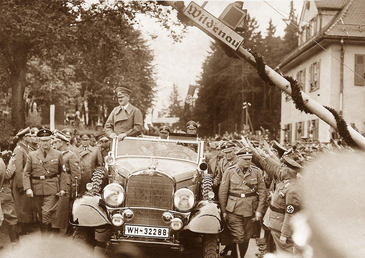 A sepia-toned photograph of Hitler enjoying a ride in his car.