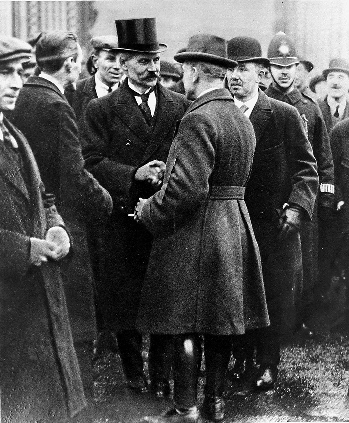 Black and white photograph of Ramsay MacDonald shaking hands with other gentlemen.