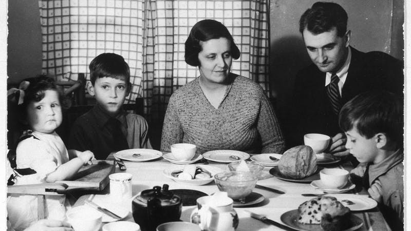 A black-and-white photograph of a family sitting around the dinner table.