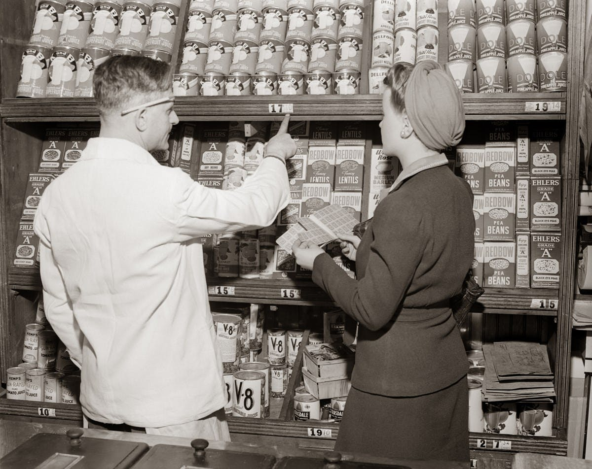 A black and white photograph of shelves of tinned goods in a grocery store. A customer holds her ration book, while a grocer points at a price.